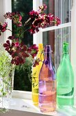 Colourful swing-top bottles and vase of flowers on window sill
