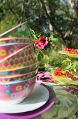 Stack of colourful bowls on summery table in garden