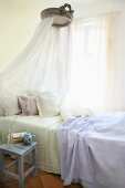 Single bed with canopy next to window in bedroom