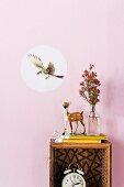 Dekorativer Aufkleber mit Vogel im Flug und Rehfigur auf Recycling Regalbox vor pastellpink getönter Wand