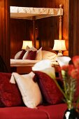Romantic hotel bed with antique-style canopy in Schloss Schauenstein; blurred scatter cushions on sofa in foreground