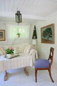 Simple, white living room with vintage furniture and large oil painting with wooden frame
