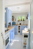 Cheerful kitchen in pastel blue with white tiled floor and pale wooden surfaces