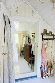 Antique chest of drawers and vintage chairs in attic dressing room with summer shoes on shoe rack in foreground