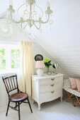 Pale pink table lamp, cosmetic mirror and cut hydrangea on white chest of drawers under sloping ceiling