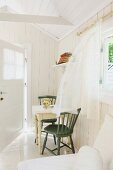 Chiffon curtains blowing in breeze in bright, summery room with open door