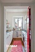 View of modern galley kitchen through open doorway