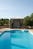 Elegant pool complex with shaded seating area in tent-style pavilion