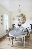 Simple Baroque furniture, glass chandelier and gilt-framed mirror in grand dining room