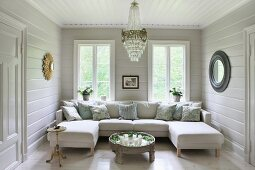 Comfortable sofa combination with two chaise elements in wood-panelled living room with chandelier and round mirrors