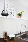 Wooden worksurface with recessed sink and designer tap fitting below white shelf