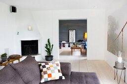 Patterned cushion on grey sofa in living room with corner fireplace and wide open doorway