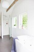 Modern bathroom with bathtub in front of floor-level shower