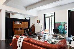 Loftwohnraum mit brauner Ledercouch und Vintage Möbeln aus verschiedenen Perioden