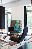 Vintage Sessel und Beistelltisch in heller Loftwohnung; Plakat mit Frauenportrait im Hintergrund