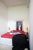 Frauenportrait in Spannrahmen hinter französischem Bett mit poppiger Tagesdecke