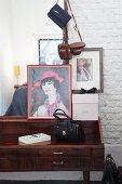 Vintage Handtasche und Frauenportrait auf 60er Jahre Schreibpult vor weisser Ziegelmauer