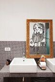 Toilettenpapier in Krokodilmaul-Figur auf gefliestem Waschtisch; Portraitzeichnung auf Spiegel mit altem Goldrahmen