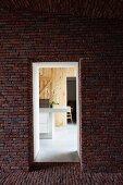 Blick durch Öffnung in Ziegelfassade auf moderne Theke in holzverkleidetem Zimmer