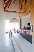 Barhocker an lange Theke aus Beton und Hängeleuchte Melone mit grossem Schirm vor Durchgang