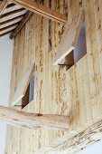 Blick auf Holzwand im Obergeschoss mit geöffneten Fensterluken aus Holz