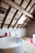 Runde Badewanne in modernem Bad im Dachgeschoss mit Holzdach