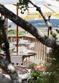Gedeckte Tische auf Holzterrasse und Blick auf Berglandschaft
