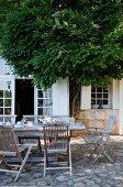 Gedeckter Tisch auf Terrasse mit Natursteinboden vor ländlichem Wohnhaus, teilweise verdeckt von einem Baum