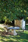 Steinplatte mit säulenartigen Fuss und Holzstühle unter dem Baum im Freien