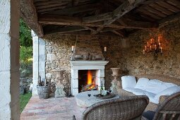 Rattan Sofagarnitur auf rustikaler Veranda mit Natursteinwand und Feuer in offenem Kamin