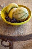 Obst in gelber Schale auf rustikaler Holz Tischplatte mit Metallbeschlag