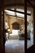 Blick durch offene Flügeltür auf Sofa gegenüber Wandtisch mit Tischleuchte in rustikalem Vorraum