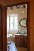 Blick durch offene Tür auf traditionellem Waschtisch mit Steinplatte in ländlichem Bad