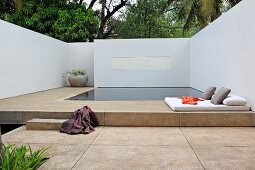 Quiet and serene geometric pool area with floor cushions and pillows surrounded by white walls overhung by trees