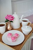 Tea service, petit fours and pink rose on a tray