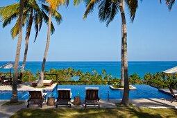 Ausblick zum blauen Meer über Poolanlage mit gepolsterten Holzliegestühlen unter Palmen