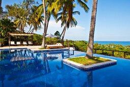 Exklusive Poolanlage mit Palme im Pool und freiem Blick zum Meer