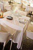 Gedeckter Tisch im Speisesaal mit weißer Tischdecke und weißen Designerstühlen
