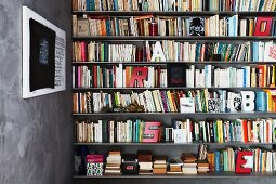 Contemporary calligraphy on grey, marbled wall and letter ornaments scattered over full book shelves