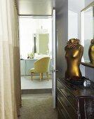 Brass torso on dresser in the hallway