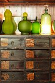 Various green bottles on rustic wooden chest of drawers