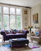 Purple sofa, ottoman and armchair in front of living room window
