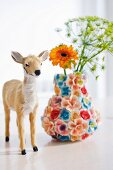 Small deer figurine next to vase covered with ceramic flowers