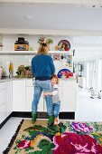 Mother working in kitchen with child hanging on leg; white corridor with colourful rug on floor