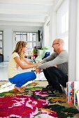 Laughing father and daughter crouching on rose-patterned kilim rug in modern, open-plan interior