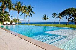 Blick über die Stufen eines langgestreckten Pools auf Palmen und Karibisches Meer