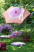 Relax on exotic furnishings in summer garden - batik parasol with bamboo base and comfortable cushions on lawn