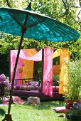 Modern couch with canopy of pink and orange fabrics in sunny garden; Oriental bamboo parasol in foreground