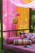 Lanterns in front of pink and orange draped canopy, modern couch exotically decorated with colourful bolsters and cushions