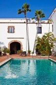 Großer Pool vor strahlend weißem Gebäude aus der Kolonialzeit mit hohen Palmen
